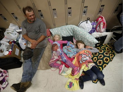 CORRECTS HURRICANE NAME TO MICHAEL NOT MATTHEW - Earnest Sweet sits while his daughters Terri, 4, center, and Anna, 7, sleep at an evacuation shelter set up at Rutherford High School, in advance of Hurricane Michael, which is expected to make landfall today, in Panama City Beach, Fla., Wednesday, Oct. 10, 2018.