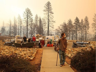 A patient walks away from a makeshift triage area as the the Feather River Hospital is evacuated during the Camp on November 8, 2018 in Paradise, California. Fueled by high winds and low humidity, the rapidly spreading Camp Fire has ripped through the town of Paradise and has quickly charred 18,000 acres and has destroyed dozens of homes in a matter of hours. The fire is currently at zero containment.
