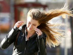 Samantha Walker does her best to battle the heavy winds in downtown Calgary on Tuesday October 17, 2017. Darren Makowichuk/Postmedia