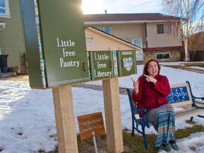 Margot Baker sits beside the little free pantry she has next to her free library at her home in Abbeydale on Wednesday January 2, 2019. Baker says she has a big spike in demand at the pantry this winter.  Gavin Young/Postmedia