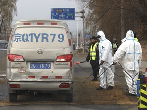 Workers disinfect passing vehicles on the outskirts of Beijing, China, on Nov. 23, 2018, after an outbreak of African swine fever in the area. Officials fear the disease could destroy Alberta's pork industry if it turns up in Canada.