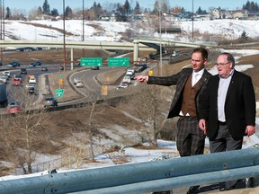 Minister of Service Alberta Brian Malkinson, left, and Transportation Minister Brian Mason walk along a pathway above Deerfoot Trail in Calgary on Thursday, March 14, 2019. The provincial government has announced major upgrades to the busy thoroughfare.