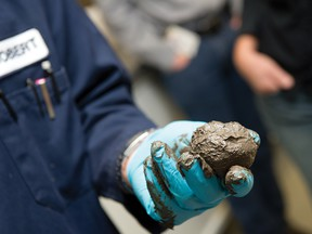 Worker at Syncrude's research facility in Edmonton shows a sample of material used at reclaimed oil sands sites.