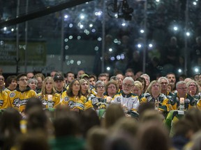 Family members and friends light candles during the Humboldt Broncos memorial service at Elgar Petersen Arena in Humboldt, SK on Saturday, April 6, 2019.