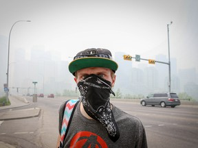 A man wears a bandana over his face as he walks along Centre Street in Calgary on Friday, May 31, 2019. Downtown is barely visible behind him, obscured by smoke from northern Alberta wildfires.