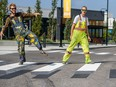 Gavin Bendig, left, and Tony Simonka of EverLine Coatings and Services pose for a photo on a 3D Crosswalk they painted at Deerfoot City on Wednesday, July 31, 2019.