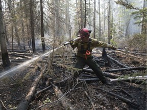 FILE - A firefighter extinguishs hotspots beside Highway 35 just south of the town of High Level on Friday, May 25, 2019.
