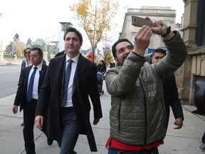 A bystander takes a selfie as Prime Minister Justin Trudeau walks to a news conference on Oct. 23, 2019 in Ottawa.