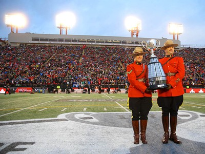 RCMP officers escort the Grey Cup championship trophy onto the field during the 107th Grey Cup CFL championship football game in Calgary on Sunday, November 24, 2019. Al Charest/Postmedia
