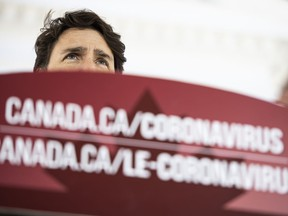 Prime Minister Justin Trudeau speaks from behind a podium bearing the hyperlink to a federal government website about the coronavirus disease during a press conference about COVID-19 in front of his residence at Rideau Cottage in Ottawa, on Sunday, March 22, 2020.