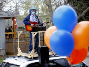 Matt Masters, founder of Curbside Concerts performs on top of his van during a Birthday Party in Calgary on Saturday, May 9, 2020. Darren Makowichuk/Postmedia