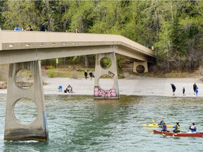 People spend the day outside on a warm spring afternoon by the Bow River on Monday, May 18, 2020.