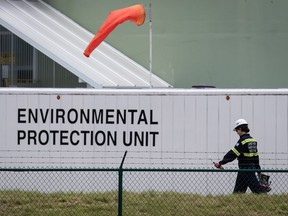 An emergency response worker carries an air monitoring device at the site of a crude oil spill at a Trans Mountain Pipeline pump station in Abbotsford, on Sunday, June 14, 2020. Trans Mountain says oil is flowing again through its pipeline after as much 190,000 litres of light crude spilled from a pumping facility in Abbotsford, B.C.
