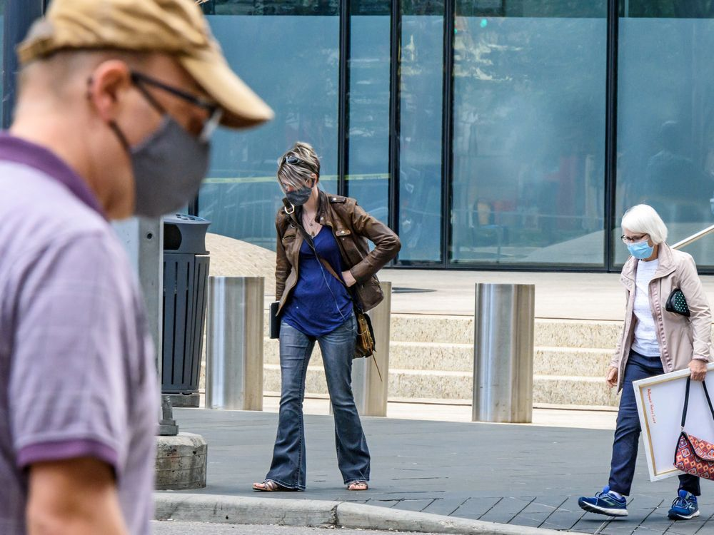 People cross the street wearing masks in Downtown Calgary on Monday, July 13, 2020.