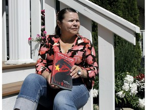 Author Karen Patterson poses with her book, Taking on China, How I Freed My Husband from Jail, outside her home on July 10, 2020. Brendan Miller/Postmedia