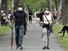People wear face masks as they walk through a city park in Montreal. In a poll of Canadians, Quebec had the rosiest outlook toward the staying power of the pandemic.
