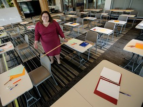 Alberta NDP Education Critic Sarah Hoffman poses in a makeshift classroom, created to illustrate the difficulties teachers and students will face in observing COVID-19 social distancing rules during a return to school this fall, in Edmonton Tuesday Aug. 11, 2020.