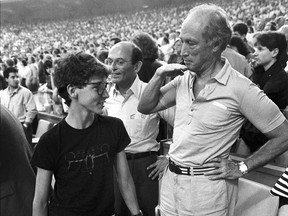 Former prime minister Pierre Trudeau shows how tall his eldest son Justin has grown in relation to himself during the seventh inning stretch at the Montreal Expos game in Montreal on April 20, 1987.