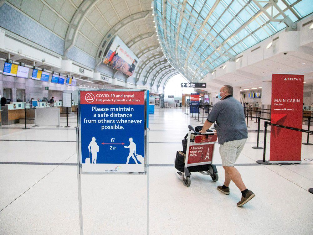 "A man pushes a baggage cart wearing a mandatory face mask as a ""Healthy Airport"" initiative is launched for travel, taking into account social distancing protocols to slow the spread of the coronavirus disease (COVID-19) at Toronto Pearson International Airport in Toronto, Ontario, Canada June 23, 2020."