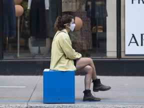 A woman wears a face mask as sits outside a clothing store in Montreal, Saturday, Aug. 22, 2020.
