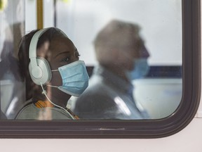 A passenger uses a Calgary transit bus while wearing a mask on Friday, September 4, 2020.