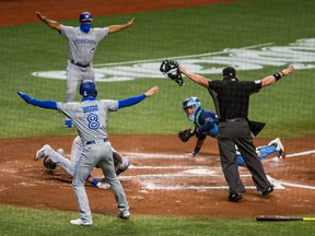 Aug 21, 2020; St. Petersburg, Florida, USA;  Toronto Blue Jays left fielder Lourdes Gurriel Jr. (13) is called safe at home by officials and teammates during the second inning of a game at Tropicana Field.  The call was later overturned. Mandatory Credit: Mary Holt-USA TODAY Sports ORG XMIT: USATSI-428686