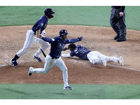 Randy Arozarena of the Tampa Bay Rays slides into home plate during the ninth inning to give his team an 8-7 victory, as Kevin Kiermaier celebrates, against the Los Angeles Dodgers in Game 4 of the World Series at Globe Life Field in Arlington, Texas, on Oct. 24, 2020.