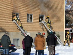Residents look on as Calgary firefighters deal with a fire in a six-unit apartment building in the 100 block of 27th Avenue N.W. on Sunday, October 25, 2020.