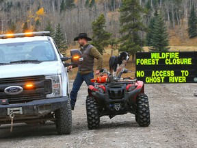 An Alberta Forestry officer chats with a local rancher at the closed road into the Ghost River Recreation Area after the status of the Devil's Head wildfire was changed to out of control on Tuesday, October 6, 2020. Crews now say the spread of the fire has slowed.