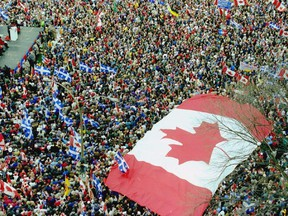 An oversized Maple Leaf flag marks a rally of huge crowds in Montreal in support of Canadian unity.