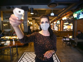 Ashlynn Harris, Events Manager at Last Best Brewing on 11 Ave SW in Calgary, demonstrates how a customer's temperature is taken upon entry to the establishment on Friday, November 13, 2020. The temperature is taken on either the forehead or wrist. Masks and sanitizer is also available upon entry and they request contact information as well.