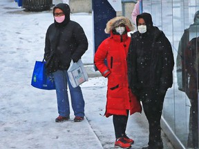 Transit riders bundle up against the wind and snow in Sunridge as a blast of winter hit Calgary on Saturday, November 7, 2020.