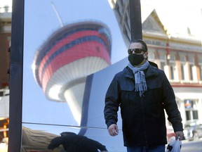 Martin Bouchard walks by a reflective mural of the Calgary Tower as COVID cases continue to increase in Calgary on Saturday, November 21, 2020.