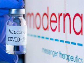 "This file photo taken on Nov. 18, 2020 shows a bottle reading ""Vaccine COVID-19"" next to the Moderna biotech company logo."