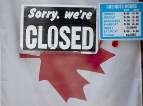 """A """"closed"""" sign hangs in a store window in Ottawa."""