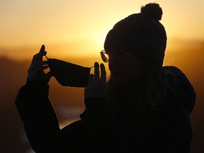 Araleigh Cranch adjusts her mask watching the sunset on Crescent Hill in Calgary on Wednesday, Dec. 2, 2020.