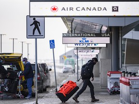 Masked travellers arrive at the International terminal in YYC (Calgary International Airport) on Friday, January 29, 2021.