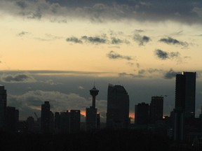 The sun sets behind the Calgary skyline on Friday, November 13, 2020 as many come to grips with new COVID-19 restriction. Some predict may see doom and gloom on the horizon while others seem to think the newest restrictions will help the extreme rise of COVID-19 cases in the city and surrounding areas. Jim Wells/Postmedia
