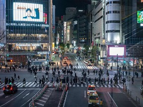 Pedestrians walk at crossing of Shibuya district in Tokyo on Jan. 8, 2021, during the first day under a state of emergency over the COVID-19 coronavirus pandemic.