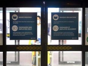 New signs are seen on the doors entering the terminal at the airport restricting access. Monday, Jan. 18, 2021.
