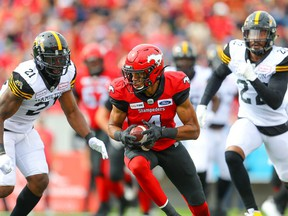 The Calgary Stampeders' Eric Rogers makes a catch in front of the Hamilton Tiger-Cats' Simoni Lawrence and Justin Tuggle on Sept. 14, 2019.