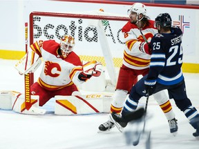 Calgary Flames goalie Jacob Markstrom (25) makes a save as defenceman Chris Tanev blocks out Winnipeg Jets forward Paul Stasny during the second period at Bell MTS Place in Winnipeg on Thursday, Jan. 14, 2021.
