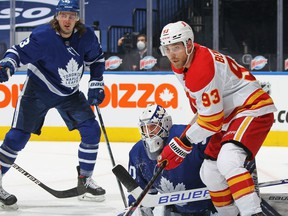 TORONTO, ON - FEBRUARY 22:  Sam Bennett #93 of the Calgary Flames looks for a puck to tip over Michael Hutchinson #30 of the Toronto Maple Leafs during an NHL game at Scotiabank Arena on February 22, 2021 in Toronto, Ontario, Canada.