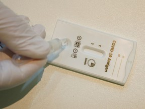 A paramedic conducts a rapid antigen test at a COVID-19 testing station in this file photo.
