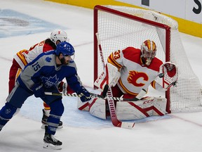 Feb. 24, 2021; Toronto, Ontario, CAN; Calgary Flames goaltender David Rittich (33) makes a glove save as Toronto Maple Leafs forward Alexander Kerfoot (15) attempts the deflection during the second period at Scotiabank Arena.