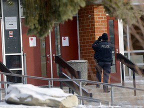 Calgary police investigate a shooting near Forest Lawn High School after two bullets hit the building on Thursday, Feb. 4, 2021. A truck parked in front also was struck.