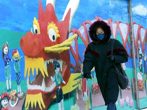 A woman passes a mural in Chinatown as celebrations to celebrate the Lunar New Year will limited due to COVID-19 in Calgary on Thursday, Feb. 11, 2021.