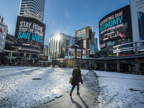 A pedestrian walks through Dundas Square in Toronto on Feb. 3. Canada has contracts to buy more vaccine doses per person than any other country, and its vaccination rates are expected to climb.