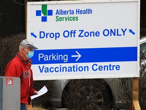 A man walks past a vaccination sign at the Richmond Road Diagnostic and Treatment Centre in Calgary on March 24, 2021.