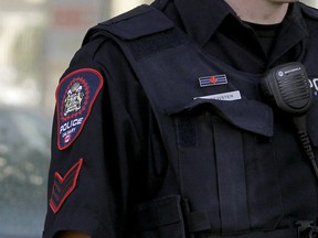 """File photo: A Calgary police officer wears a """"thin blue line"""" patch above his nametag."""
